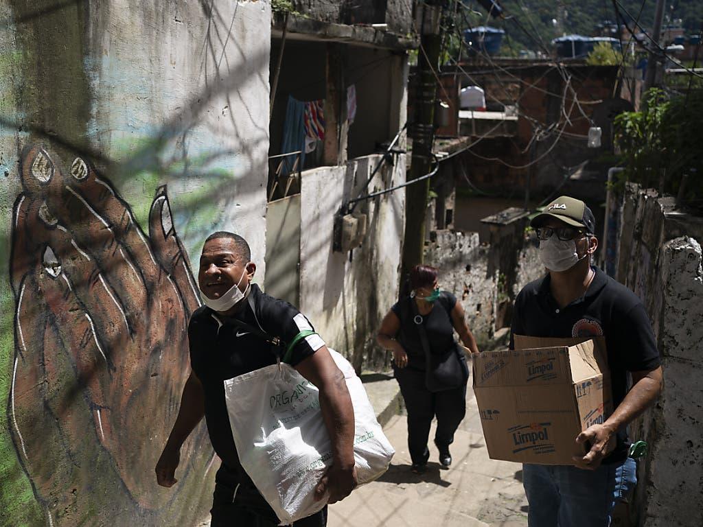 Freiwillige bringen Pakete mit Seife und Waschmittel in einen Slum in Rio de Janeiro.