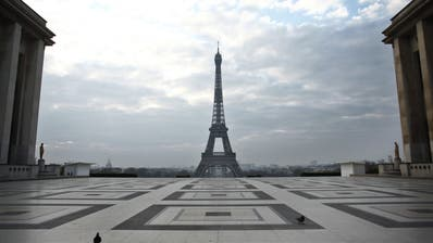 Tauben vor dem Eiffelturm: Wo sich sonst Menschenmassen tummeln, herrscht in diesen Tagen eine gespenstische Ruhe. (Thibault Camus / AP)