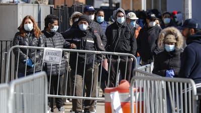 Patienten mit Gesichtsschutz vor einem Spital in New York: Die Millionenstadt ist derzeit der Corona-Hotspot der USA. (John Minchillo / AP)