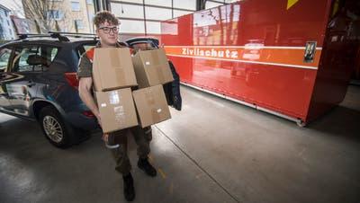 Ein Zivilschützer lädt Kisten mit Atemmasken aus. ((Bild: Reto Martin))