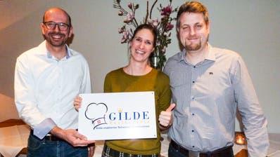 «Gilde»-Botschafter Claude Tappolet mit den ausgezeichneten Gastgebern Bianca und Stephan Roth. ((Bild: Kurt Lichtensteiger))