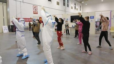 In einem temporären Spital in Wuhan macht medizinisches Personal mit Corona-PatientenGymnastikübungen. (Zhang Junjian/AP)