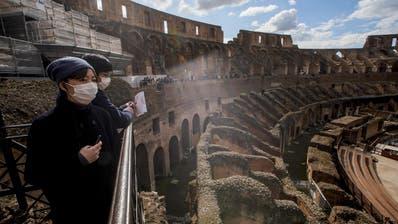 Touristen mit Maske im Kolosseum von Rom. (Bild: keystone)