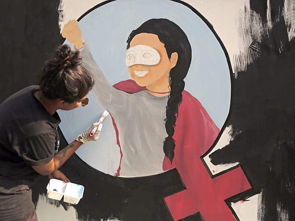 In Bangladesch malt eine Künstlerin zum Internationalen Frauentag in Dhaka ein Wandbild.