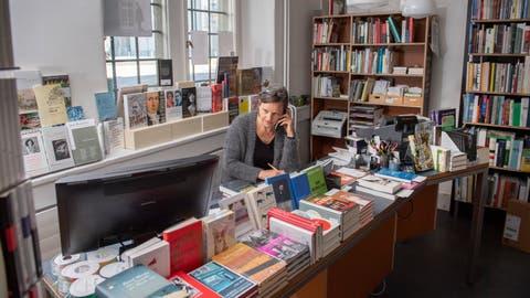 Leonie Schwendimann von der St.Galler Buchhandlung zur Rose deponiert bestellte Bücher zum Abholen im Hauseingang. (Bild: Urs Bucher)