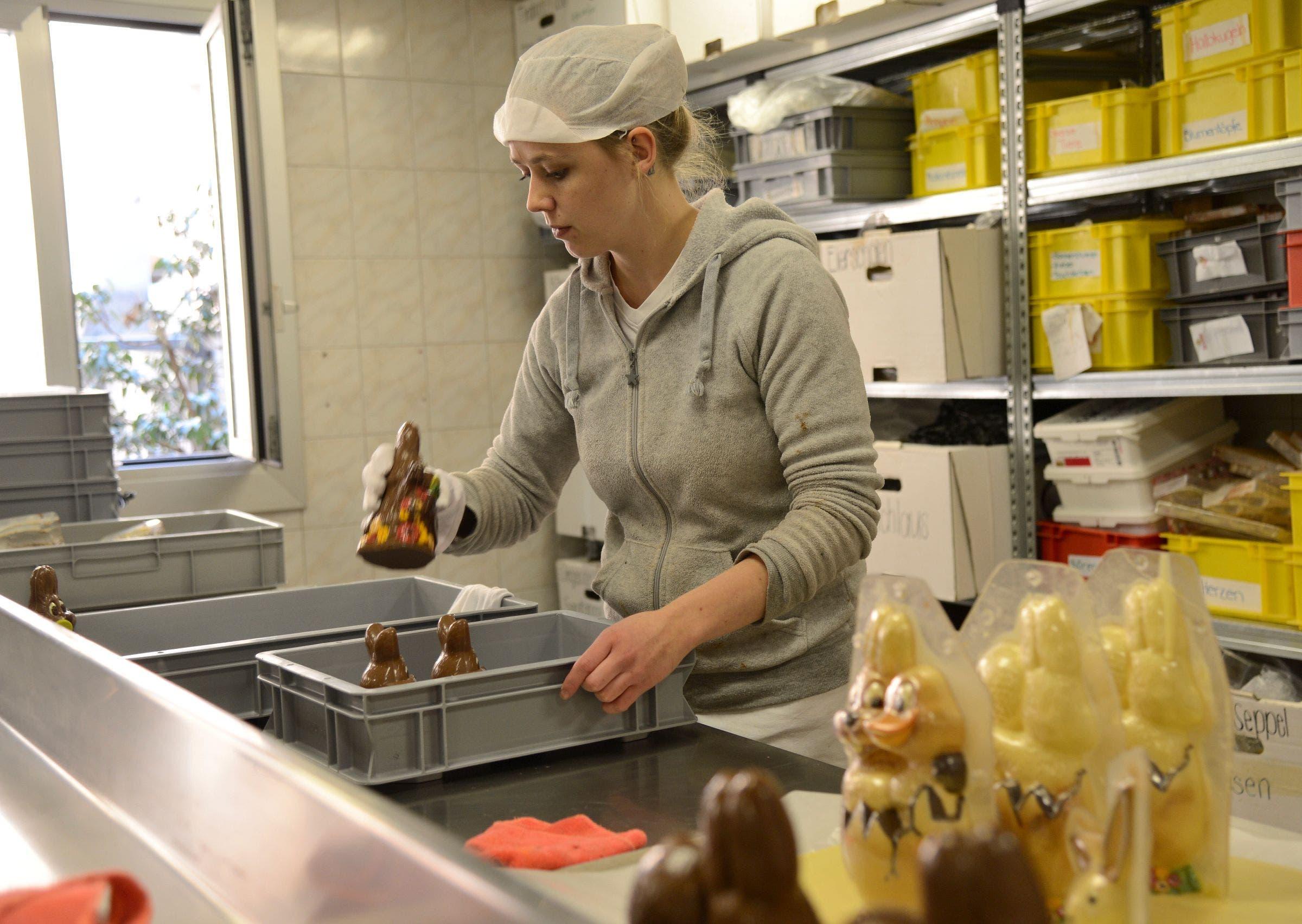 Angie Imholz hilft beim Herstellen der verschiedenen Osterhasen aus brauner und weisser Schokolade.