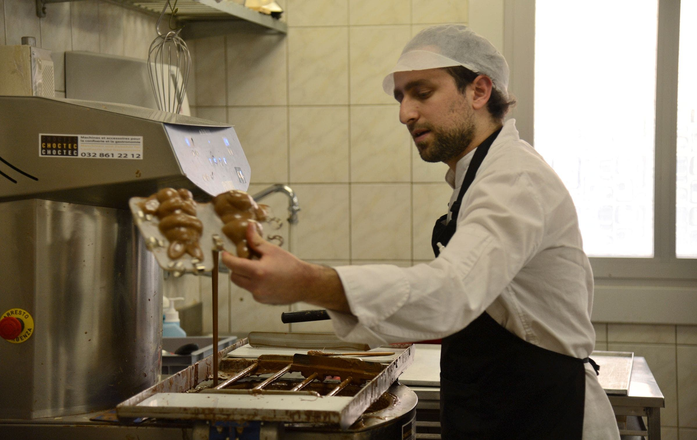 Die Temperatur muss stimmen: Stefanos Kostas befüllt die Plastikformen mit flüssiger Schokolade.