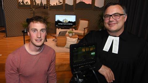 David Ohnemus und Lukas Butscher posieren vor der Kulisse im temporären Fernsehstudio in der Chrischona. ((Bild: Manuel Nagel))
