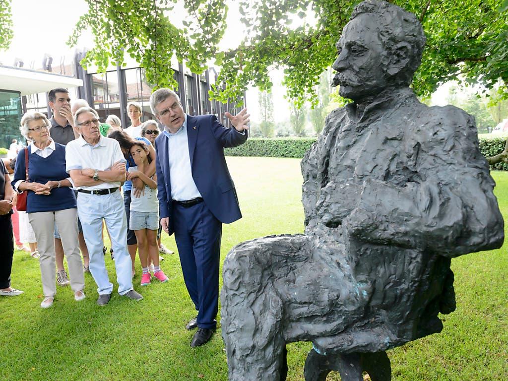 IOC-Präsident Thomas Bach neben einer Statue von Pierre de Coubertin, dem «Erfinder» der modernen Olympischen Spiele