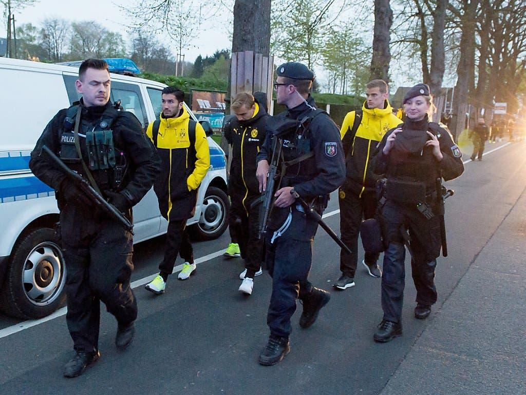 Sichtlich geschockt werden BVB-Spieler nach dem Sprengstoffanschlag auf ihren Mannschaftsbus von Polizisten bewacht und begleitet