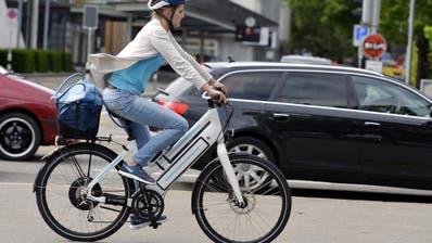Prägen das Strassenbild immer mehr: Eine Elektrobike-Fahrerin fährt auf einer Strasse in Zürich. (Bild: Walter Bieri / Keystone)