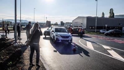 Mit Helm und Warnweste: Gemeindepräsident Kurt Baumann überreicht der ersten Autofahrerin, welche die Umfahrungsstrasse Richtung Eschlikon befährt, einen Blumenstrauss. ((Bild: Olaf Kühne))