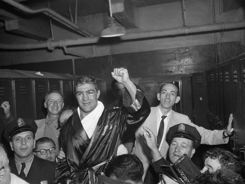Ein stark gezeichneter Rocky Marciano feiert in der Umkleidekabine des Municipal Stadium in Philadelphia den Weltmeistertitel