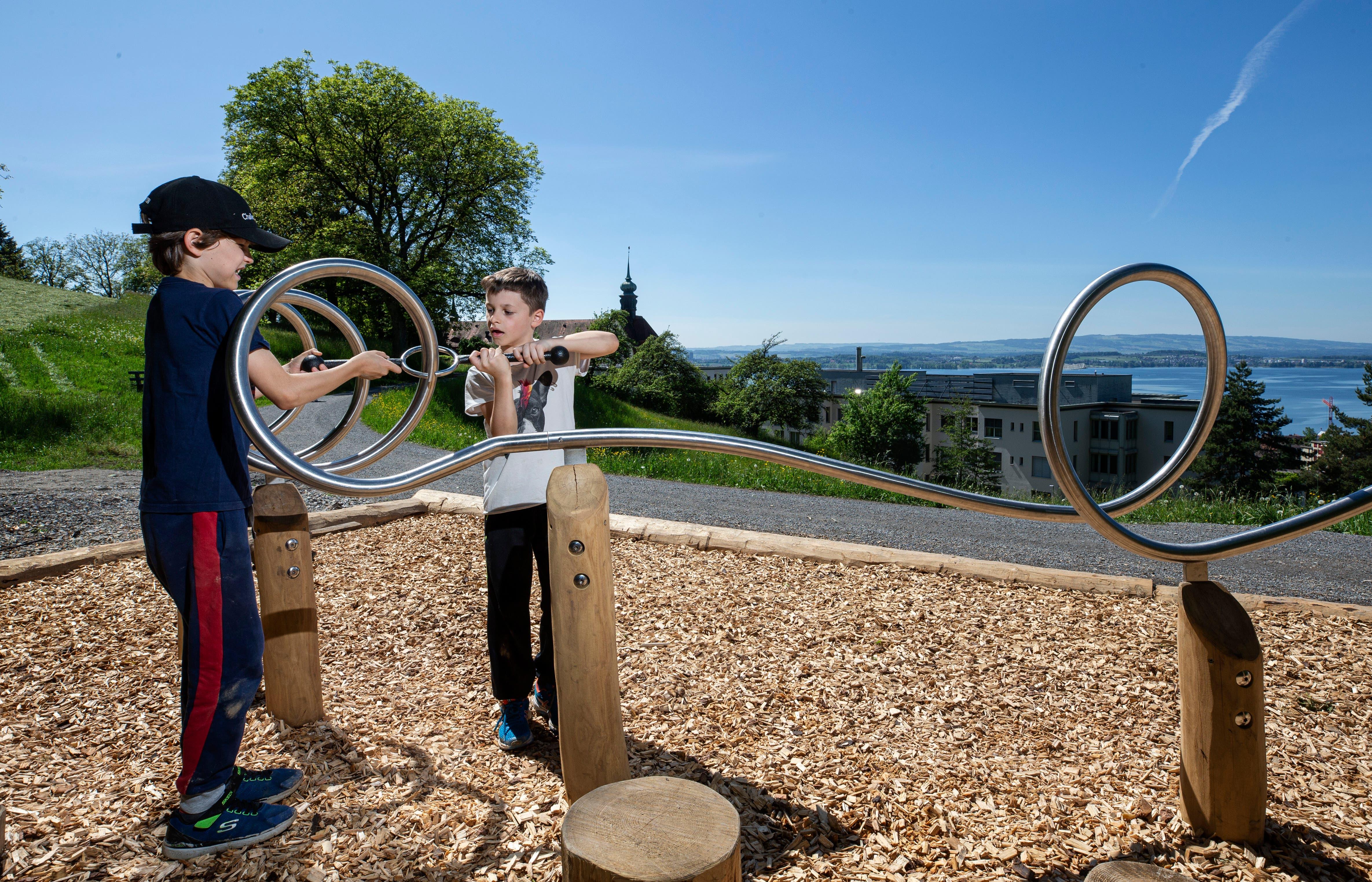 Der neue Zuger Waldparcours verbindet Sport und Kultur: Beim Posten Nummer 11 am Waldrand ist Geschicklichkeit gefragt. Die beiden neunjährigen Schüler Dominik und Liam aus Zug üben sich konzentriert am «Geduldsfaden».