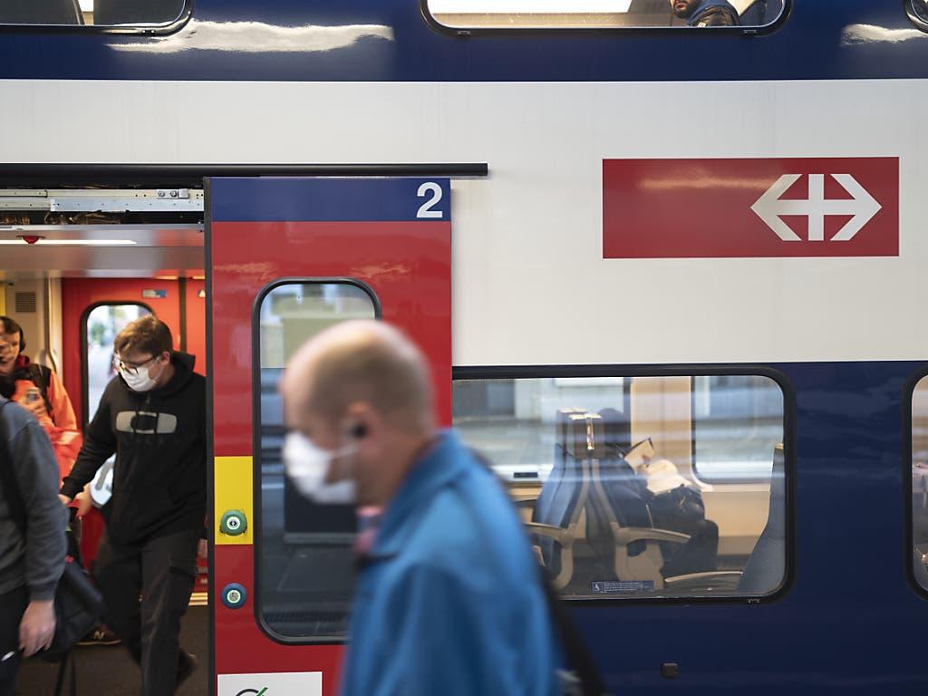 Pendler mit und ohne Schutzmasken fahren in einer S-Bahn nach dem Corona-Lockdown am Hauptbahnhof in Zürich.
