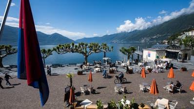 Einheimische und Touristen geniessen das schöne Wetter an der Uferpromenade in Ascona. (Bild: Samuel Golay / Keystone (17. Mai 2020))