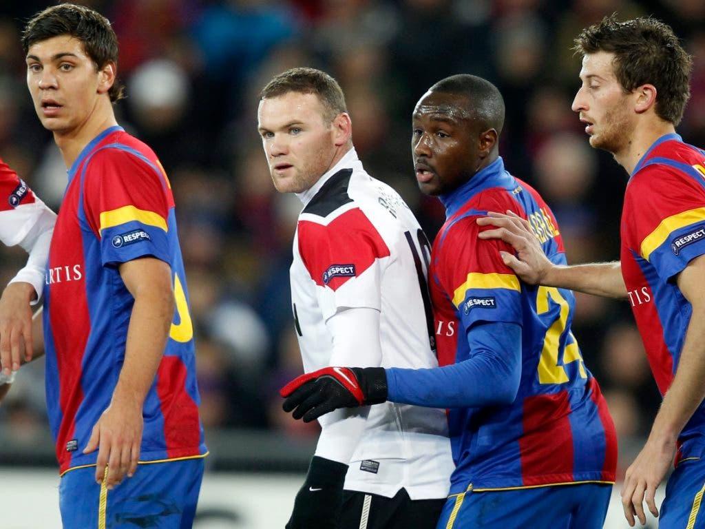 Manchesters Wayne Rooney umgeben von den Basler Spielern Aleksandar Dragovic (links), Cabral and David Abraham (rechts)