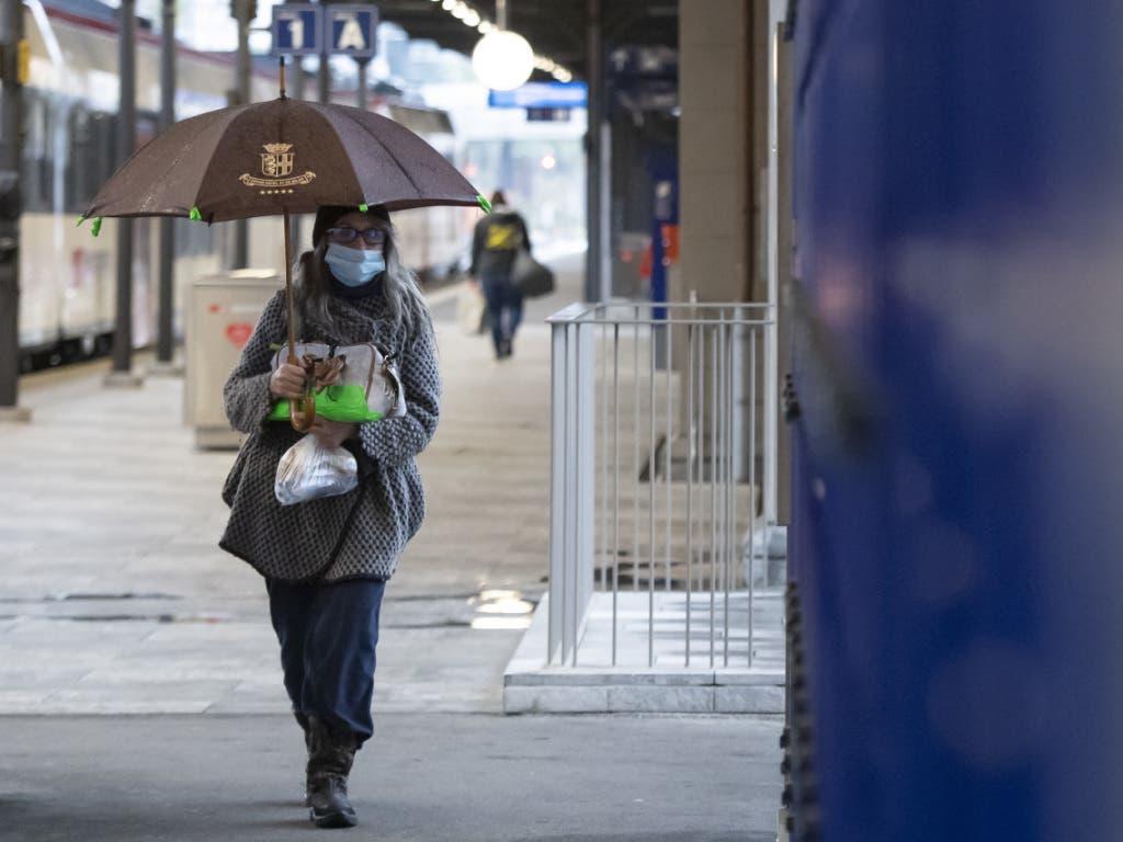 Eine Frau mit Hygienemaske läuft das Perron beim Bahnhof Locarno entlang.