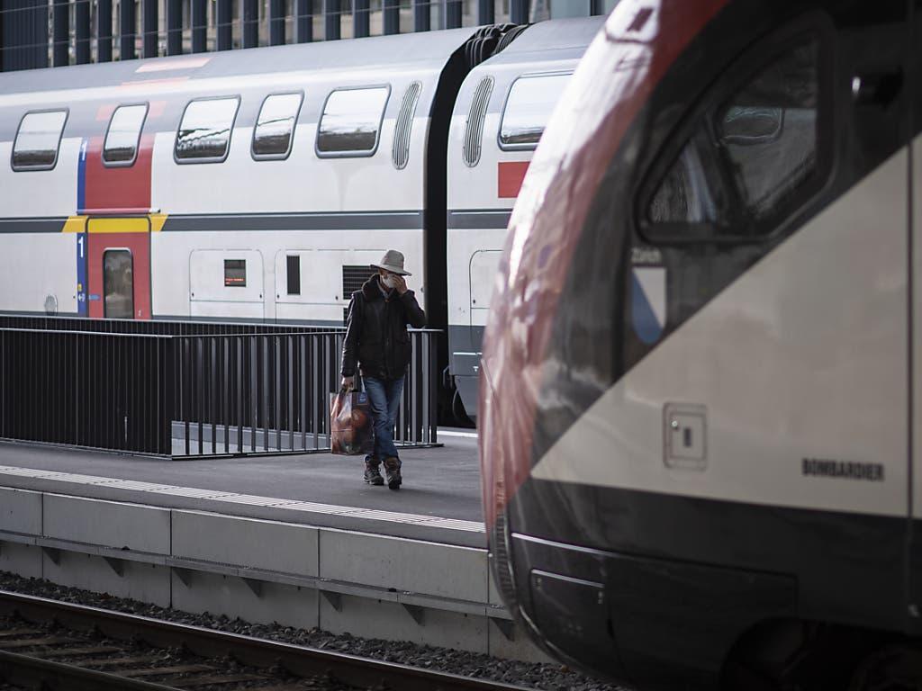 Ein Mann mit Maske auf dem Weg zum Zug am Bahnhof in St. Gallen.