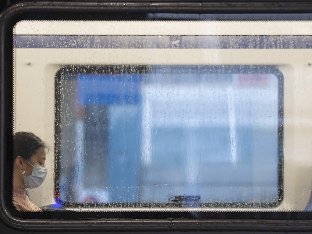 Noch seltene «Einzelmasken»: Eine Frau mit Hygienemaske in einer S-Bahn am Bahnhof Locarno.