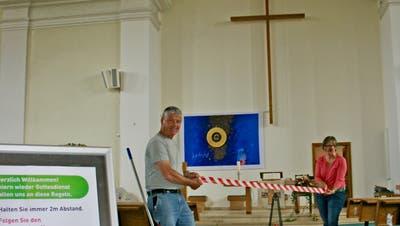 Boden markieren und Sitzplätze punktieren: Die Mesmer Werner Häne und Heidi Ünes rüsten die Kirche Wattwil aus. (Bild: PD)