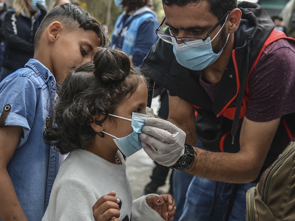 Die Maske bei diesem Migrantenkind muss sitzen: Die griechischen Behörden haben rund 400 Migranten aus dem überfüllten Lager von Moria auf Lesbos aufs Festland gebracht.