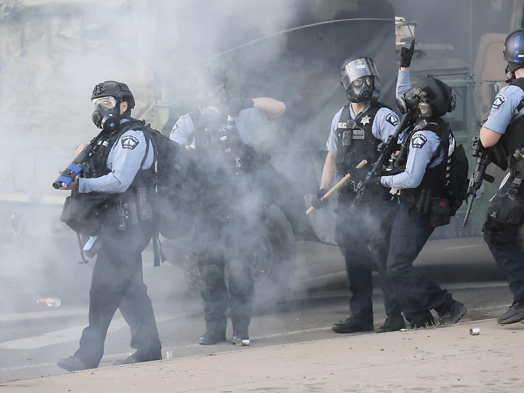 Polizisten versuchen in Minneapolis, die Proteste einzudämmen und die Ausgangssperre durchzusetzen.