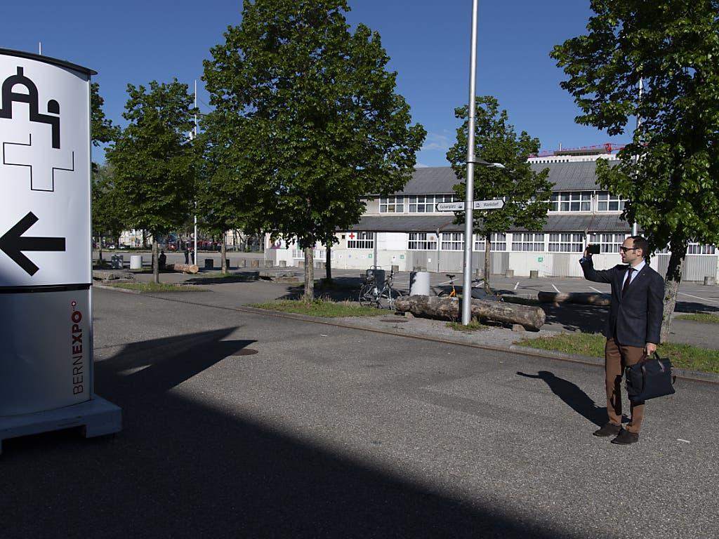 Der Berner FDP-Nationalrat Christian Wasserfallen macht ein Foto des Geländes am ersten Tag der ausserordentlichen Session der Eidgenössischen Räte zur Corona-Krise in einer Ausstellungshalle der Bernexpo in Bern.