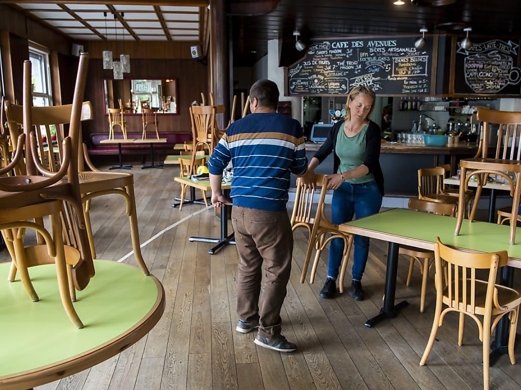 Ein Ehepaar richtet sein Restaurant in Lausanne den Corona-Vorschriften entsprechend her für die Wiedereröffnung am 11. Mai.