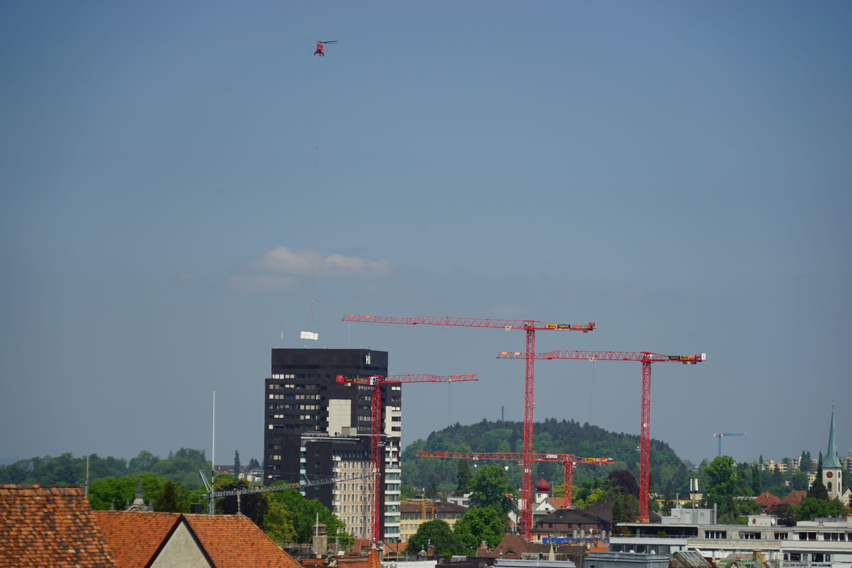 Der Heli mit der weissen Aussenlast über dem Areal des Kantonsspitals. Wie die Kräne zeigen, wird dort derzeit heftig gebaut. Der Helikopterflug stand aber nicht in Zusammenhang mit diesem Projekt.
