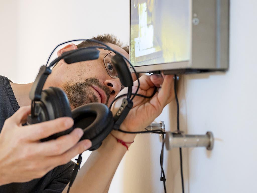 Multimediaspezialist Daniel Dressel demontiert als Hygienemassnahme die Kopfhörer einer Installation vor der Wiedereröffnung der Ausstellung «Amuse-bouche. Der Geschmack der Kunst» im Museum Tinguely.