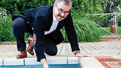 Rorschachs Stadtpräsident Röbi Raths testet die Wassertemperatur im grossen Becken. (Bild: Rudolf Hirtl)