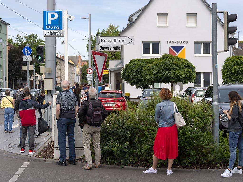 Am Tag der Wiedereröffnung der Grenzen bildet sich eine lange Warteschlange vor einem Paketshop im deutschen Weil am Rhein.