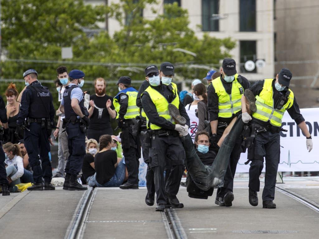 Polizisten tragen einen Aktivisten der Umweltbewegung Extinction Rebellion von der Quaibrücke in Zürich.