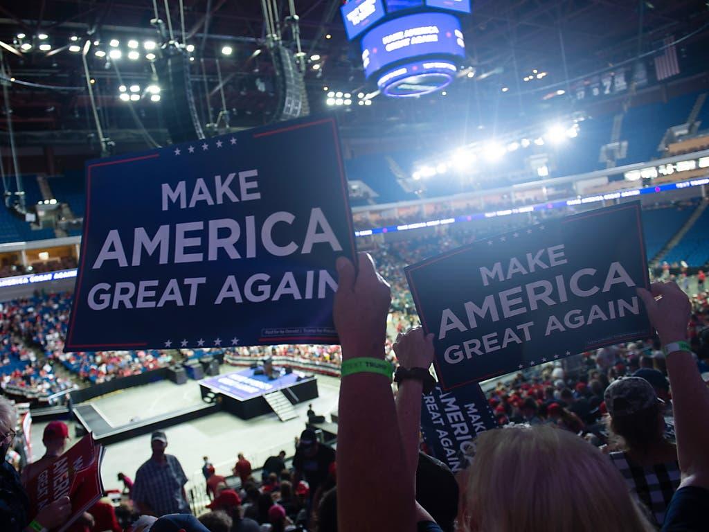 Make America great again: Unterstützer von US-Präsident Donald Trump halten in Tulsa Schilder in die Höhe. Im Hintergrung sind leere Sitze zu sehen.