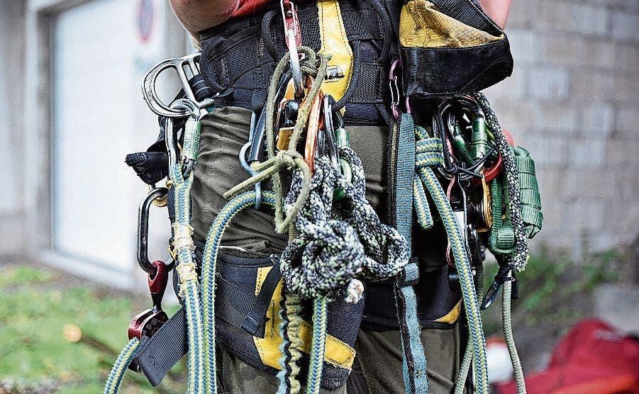Am Klettergurt hängt viel Sicherungsmaterial und Werkzeug.
