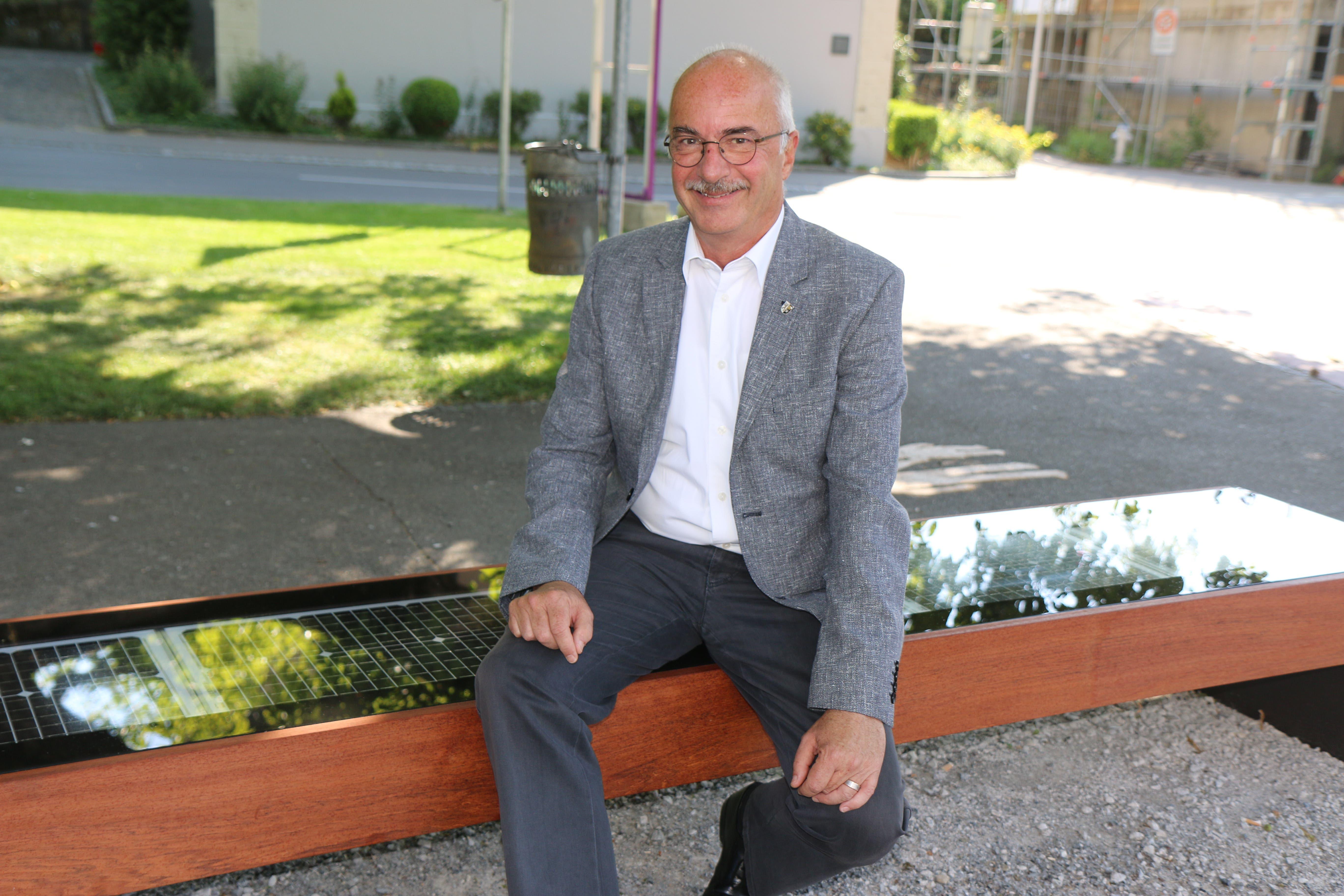Daniel Meili, Stadtpräsident ad interim, sitzt auf dem neuen Photovoltaik-Wifi-Bänkli nahe dem Alterszentrum Sonnenhof.