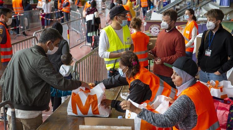 Zum letzten Mal sind am Samstag in der Eisbahn von Les Vernets bei Genf 3000 Hilfspakete an Bedürftige verteilt worden. (Salvatore Di Nolfi / Keystone)