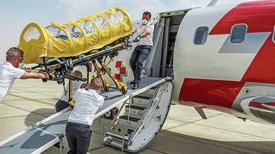 Eine Patient in einer Isolations-Einheit wird in einen Ambulanzjet verladen.