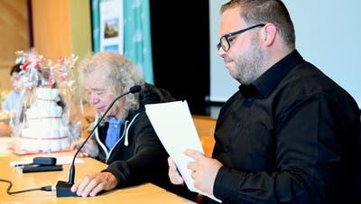 Jakob Auer rückt für seinen Nachfolger Lukas Auer das Mikrofon zurecht. Im Hintergrund steht die Windeltorte. (Helio Hickl)
