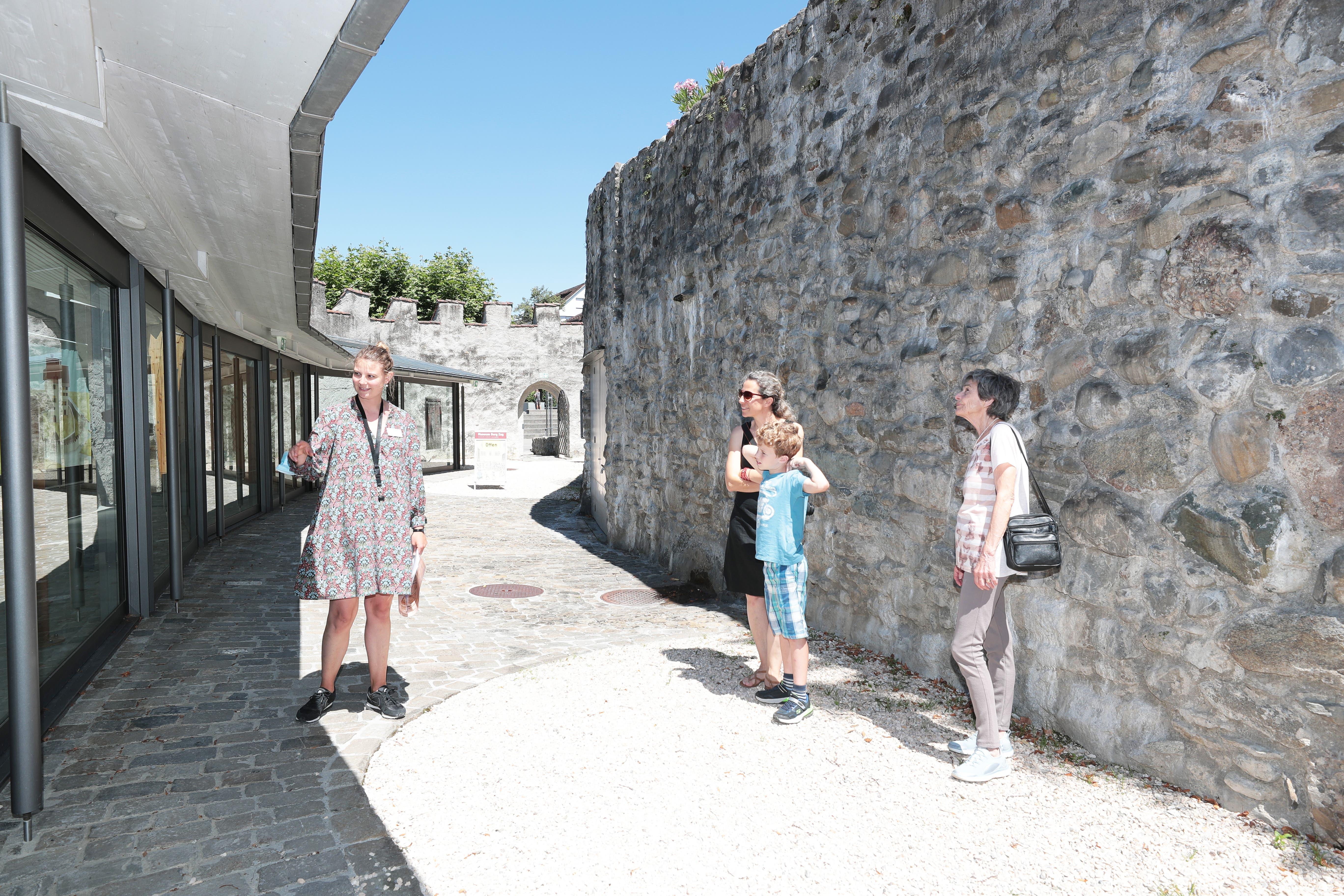Sophia Aschwanden vom Museum Zug (links) erklärt Michèle Jörg (schwarzes Kleid, mit Fabio Dittli) und Marlen Wildher, worum es geht.
