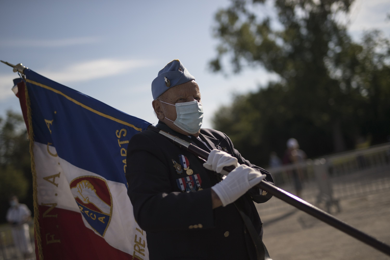 Ein Veteran marschiert bei der Militärparade mit Maske mit.