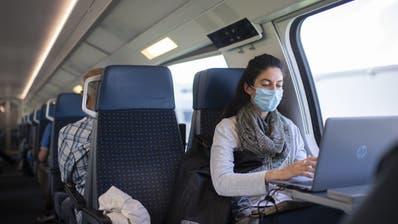 Eine Frau mit Schutzmaske im Zug (Gian Ehrenzeller / KEYSTONE)