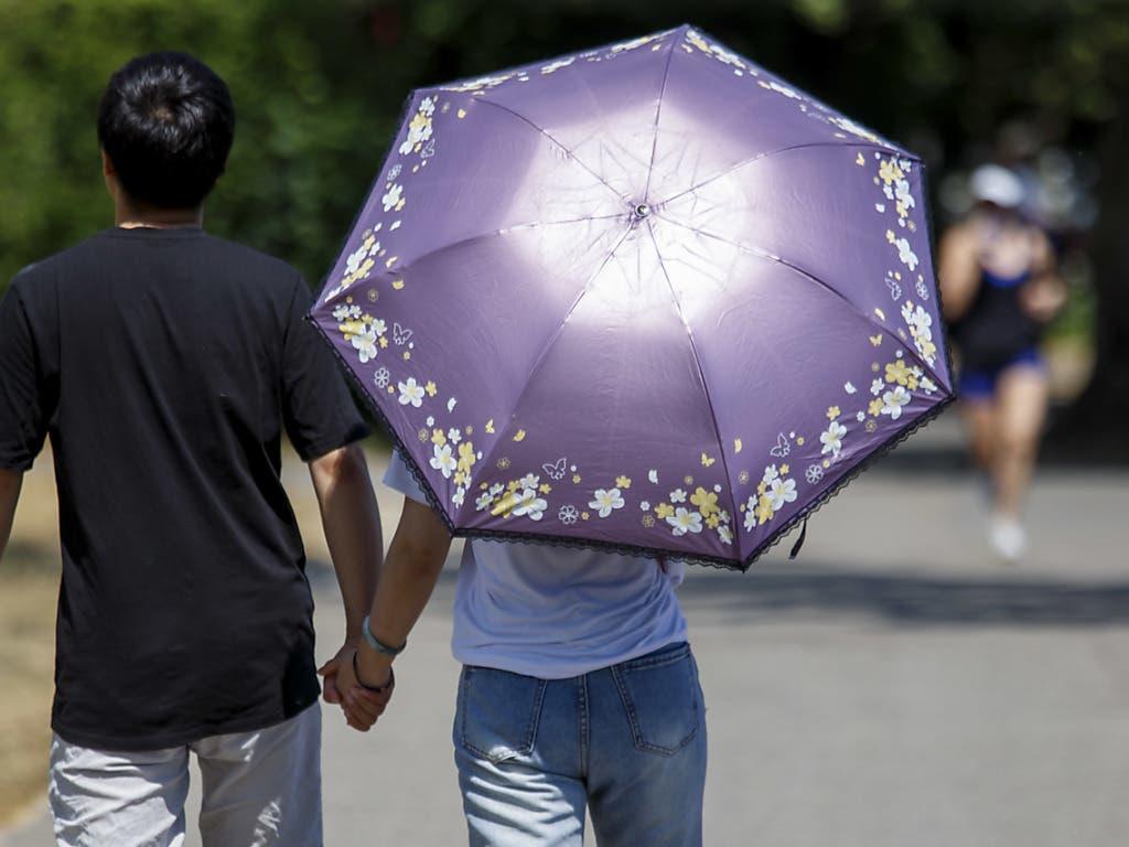 Schutz vor der Sommerhitze unter einem Schirm auf einem Spaziergang in Genf.