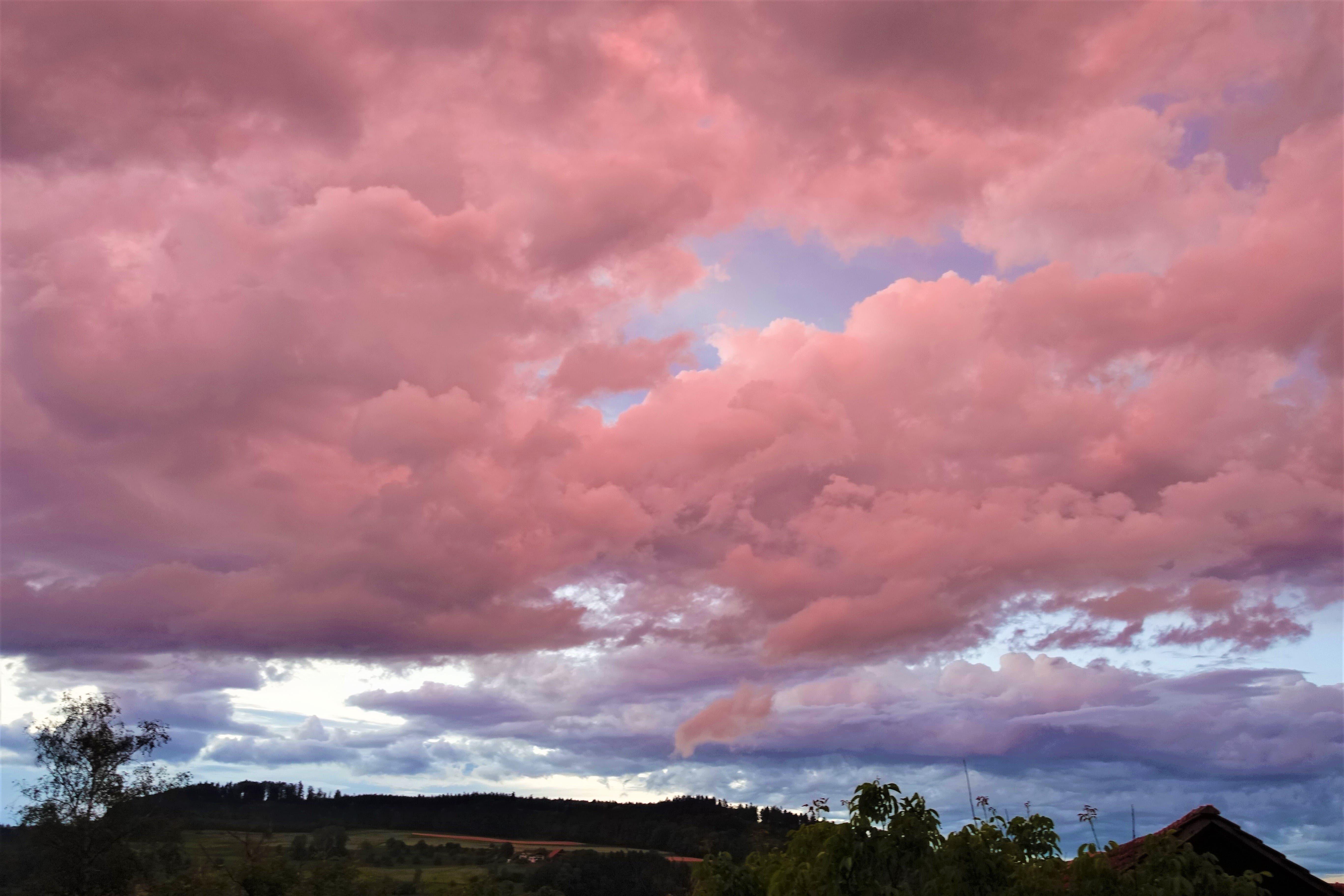 Die untergehende Sonne färbt die aufkommenden Gewitterwolken rötlich.