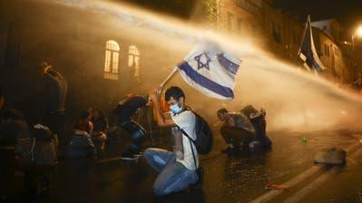 Wasserwerfer gegen Wut: Viele Israelis lassen sich von der Polizei nicht abschrecken. (Bild: Oded Balilty/AP (Jerusalem, 18. Juli 2020))