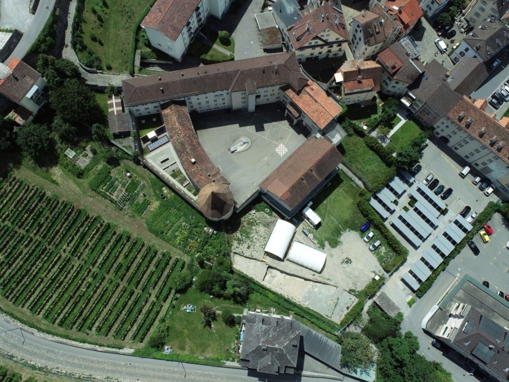 Das ehemalige Churer Gefängnis Sennhof im Zentrum des Bildes. Die Ausgrabungen finden ausserhalb der Mauern statt unter den zwei weissen Zeltdächern.