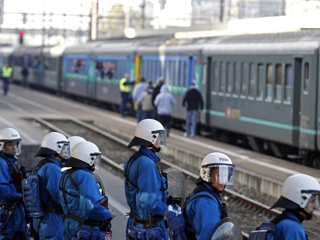 Polizeikräfte bewachen einen Fanzug am Bahnhof Zürich-Altstetten.