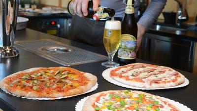 Aurèle Meyer von der Brauerei Locher serviert Pizze aus Biertreber. (Karin Erni)