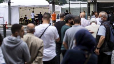 Reisende warten auf einen Coronatestam Flughafen Köln: In Deutschland steigen die Coronazahlen wieder. (Marius Becker / AP)